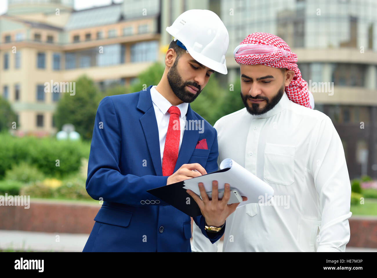 Discussing details. Horizontal shot of an outdoor meeting of an engineer and his Saudi client - Stock Image