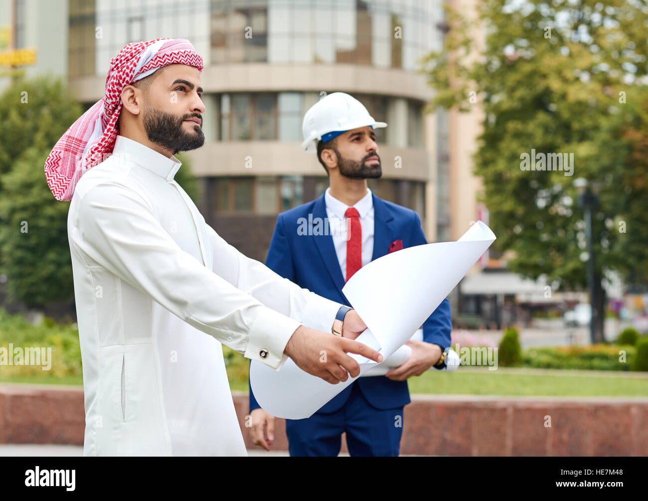 Keeping construction under control. Saudi businessman holding a blueprint looking at the building his architect - Stock Image