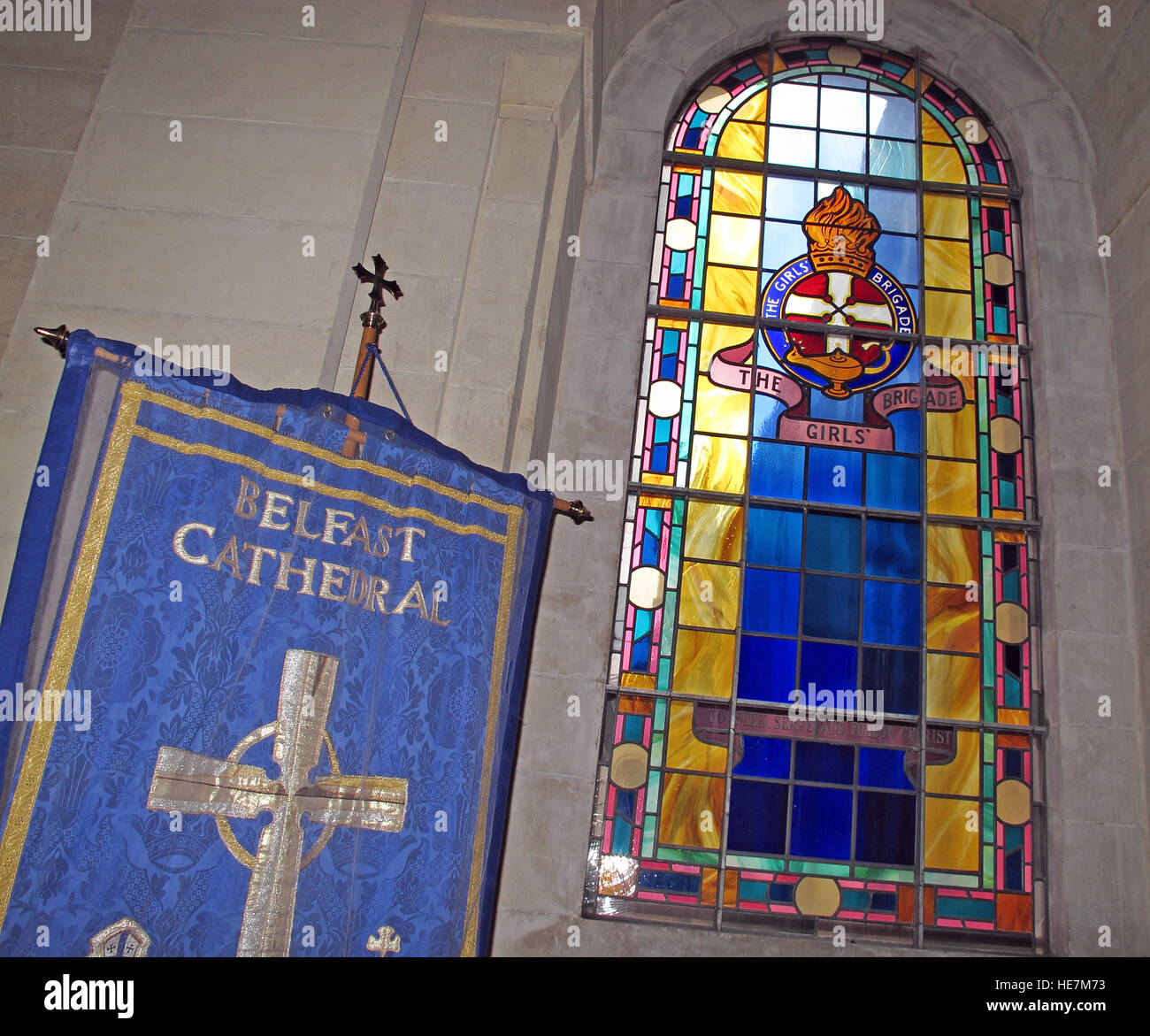 St Annes Belfast Cathedral Interior,Girls Brigade stained glass window and flag - Stock Image