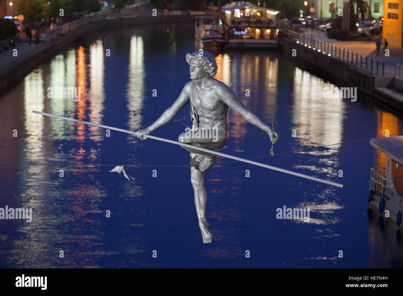 """""""Man crossing the River"""" at night, balancing sculpture by Jerzy Kedziora in Bydgoszcz, Poland, commemorates the Stock Photo"""
