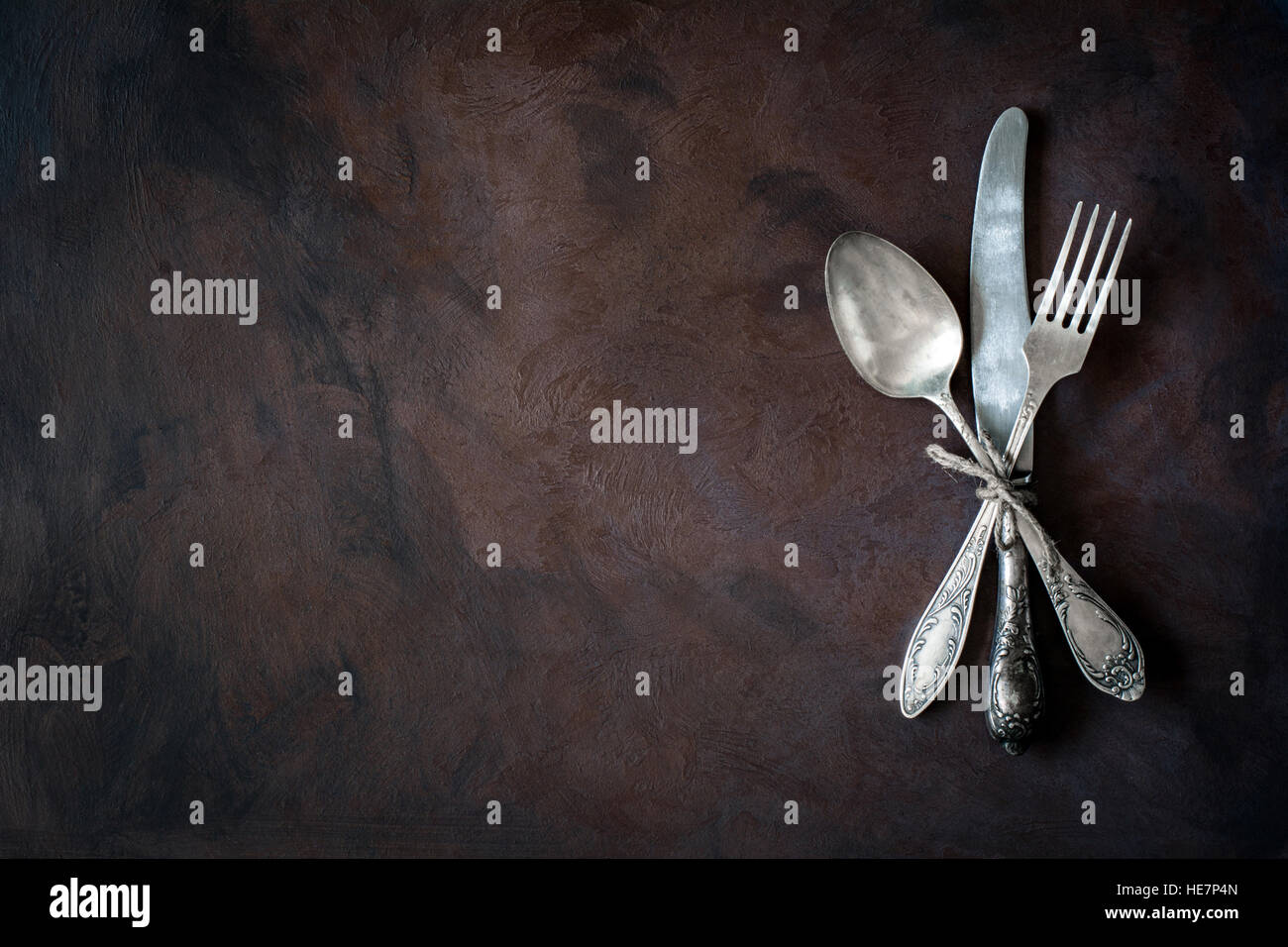 Vintage cutlery / silverware on dark background with copy space for text - Stock Image