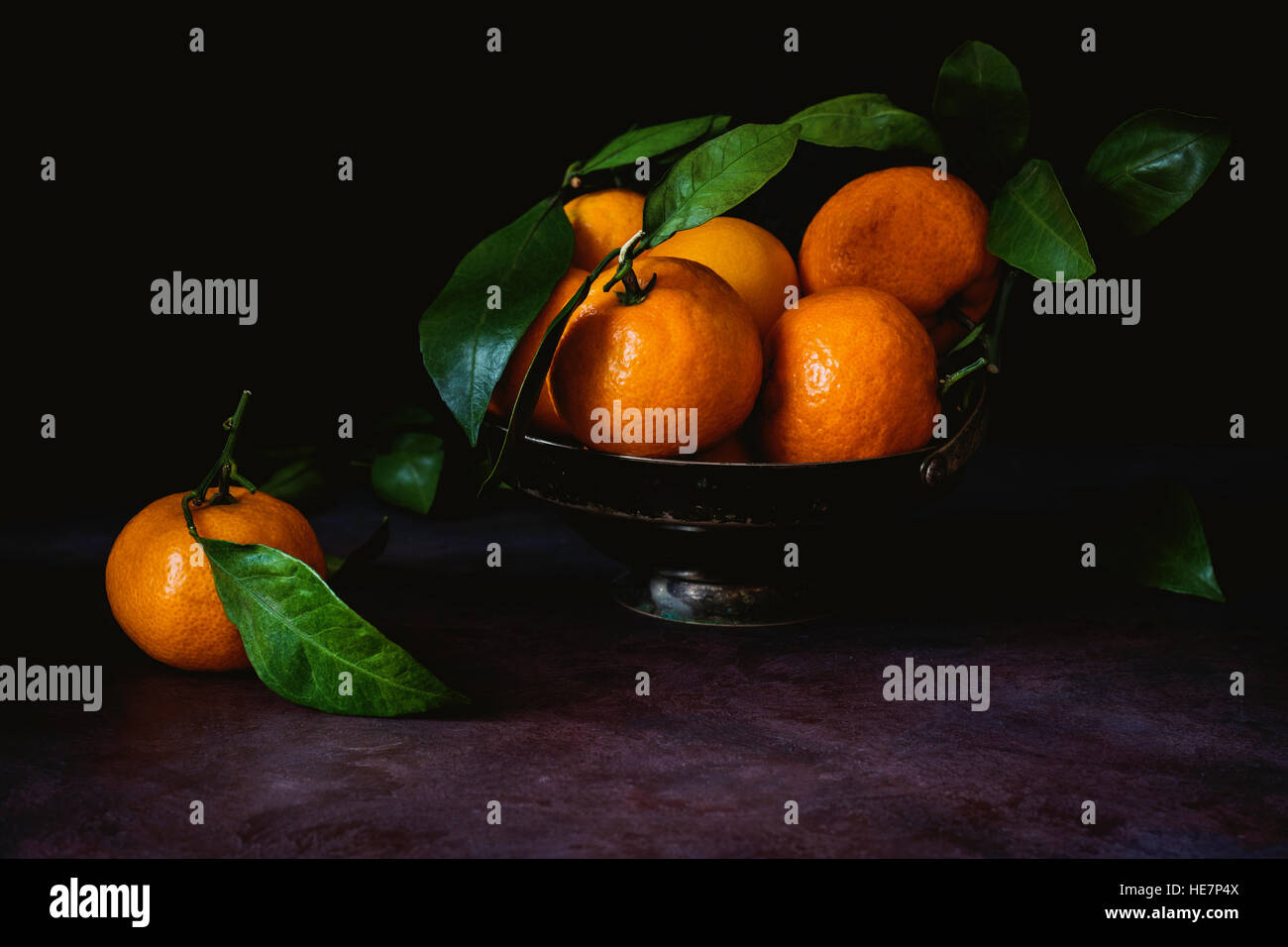 Still life of fresh tangerines with green leaves in vintage metal bowl. Toned image, low key technique (chiaroscuro). - Stock Image