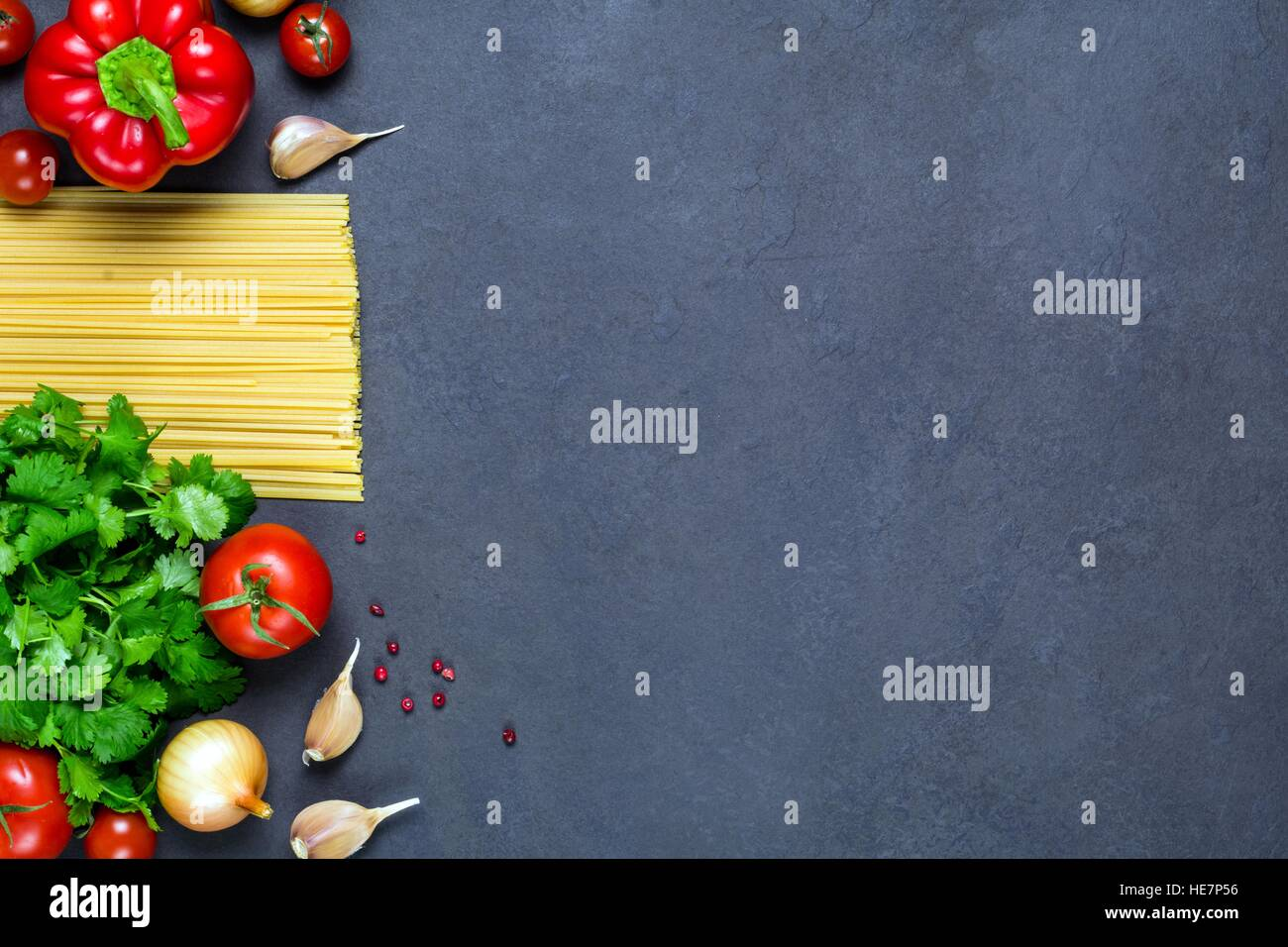 Pasta, spices and vegetables on slate background - cooking ingredients for italian cuisine. Copy space for text. - Stock Image