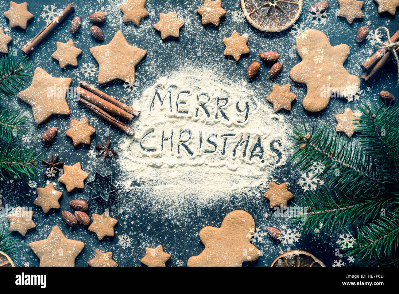 Merry Christmas greeting written on flour on blackboard. Frame with gingerbread stars cookies, gingerbread man cookies - Stock Image