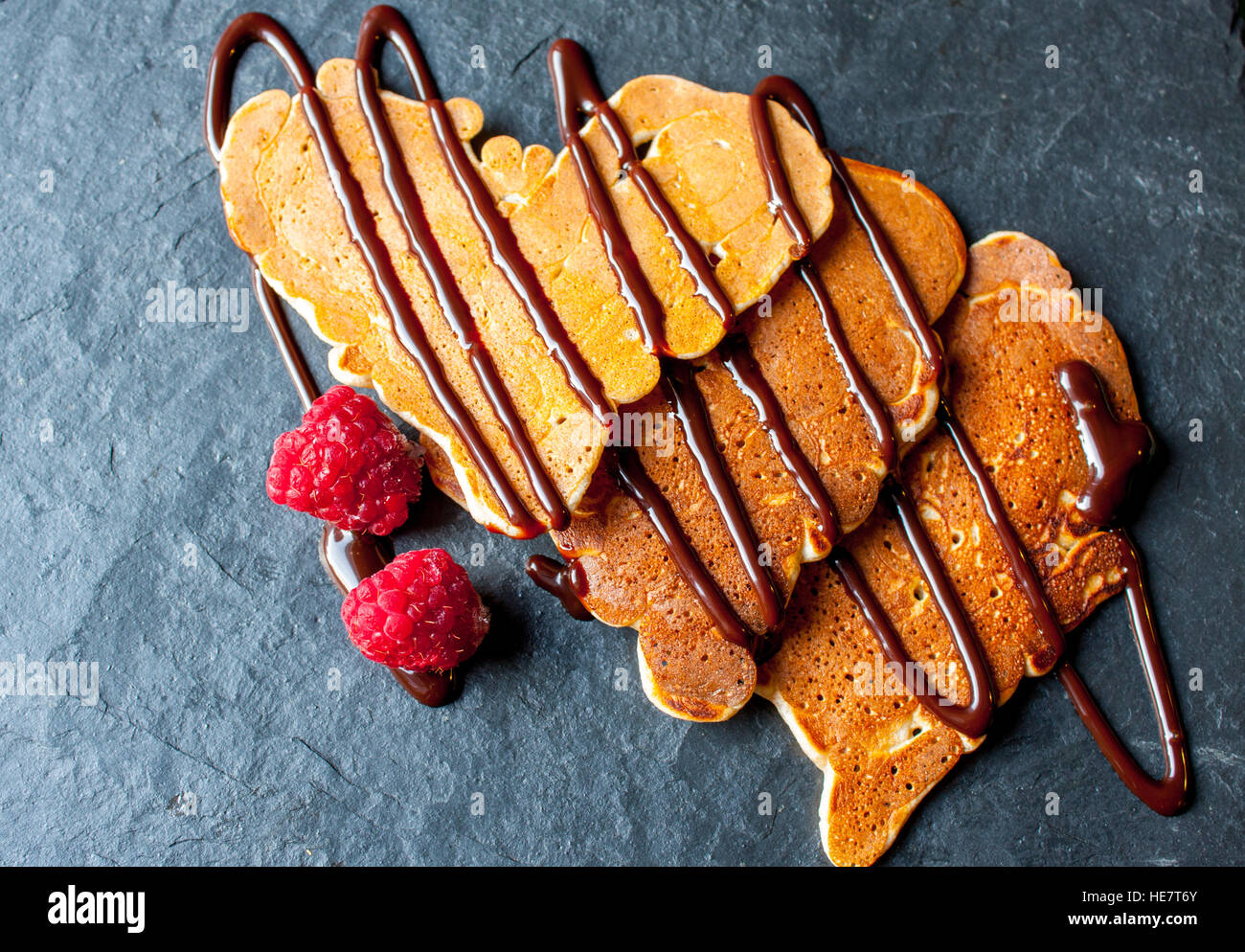Pancakes in the shape of a heart with chocolate syrup and raspberries on valentine's day. Stock Photo