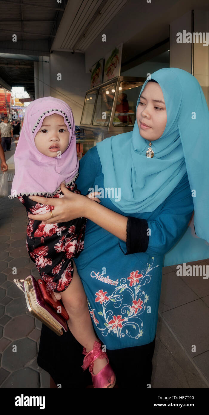 Young Muslim Mother And Baby Daughter Both Wearing Traditional