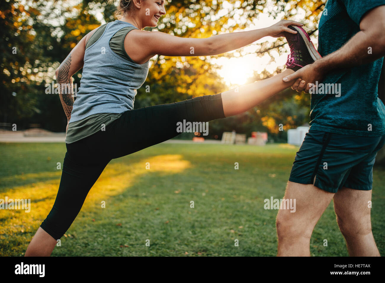 Fit young woman doing stretching exercises with the help of a personal trainer in park. Coach holding leg of female. - Stock Image