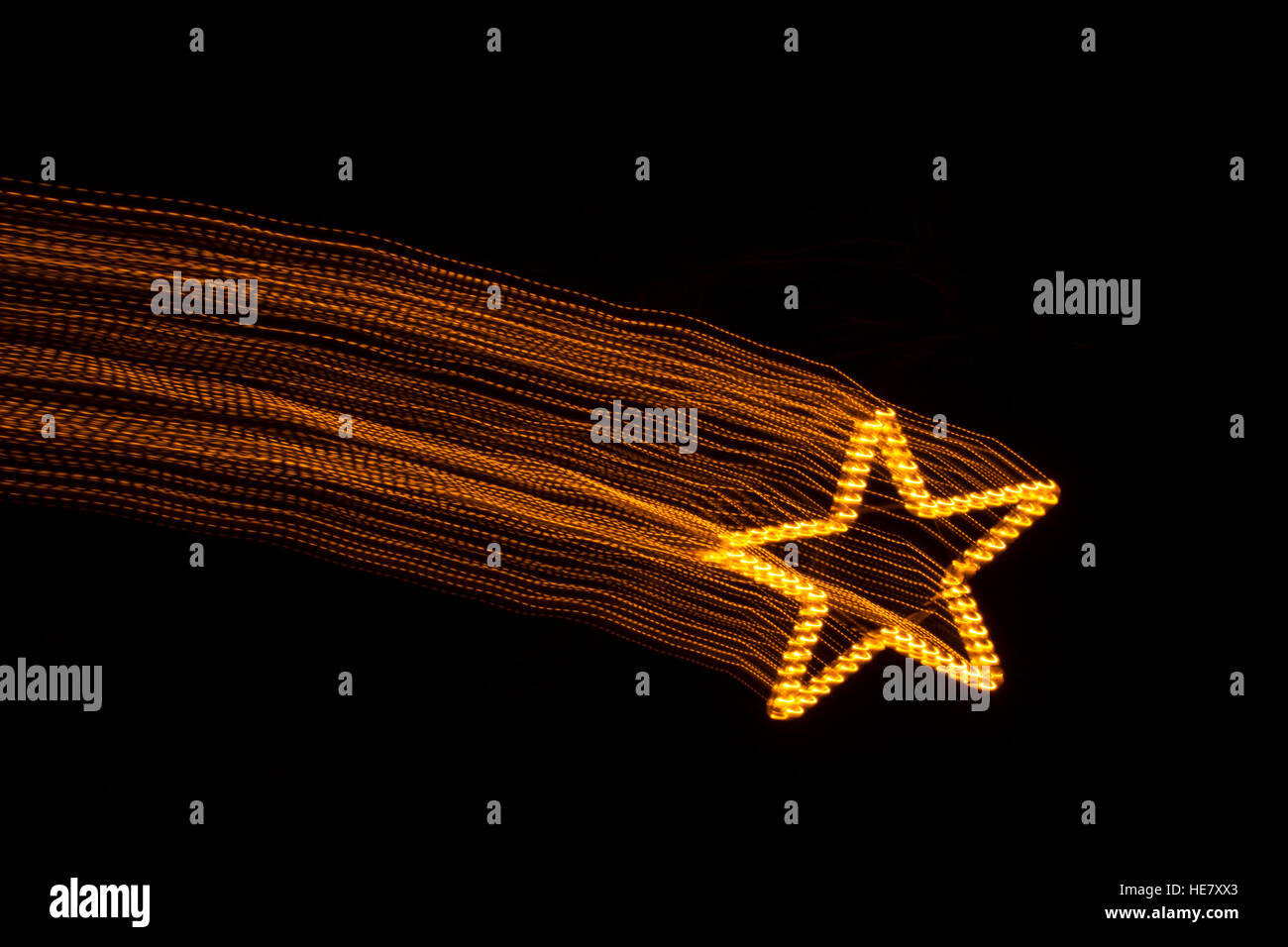 Star shaped Christmas decoration made to look like falling star by light painting. - Stock Image