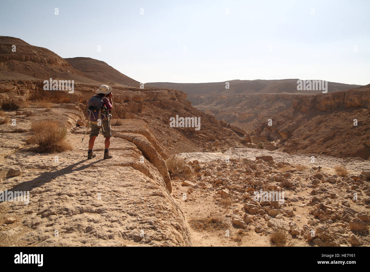 A 69 year old woman hiker takes pictures of the dry waterfall and dry riverbed of Nachal Kamai. The rugged Negev - Stock Image