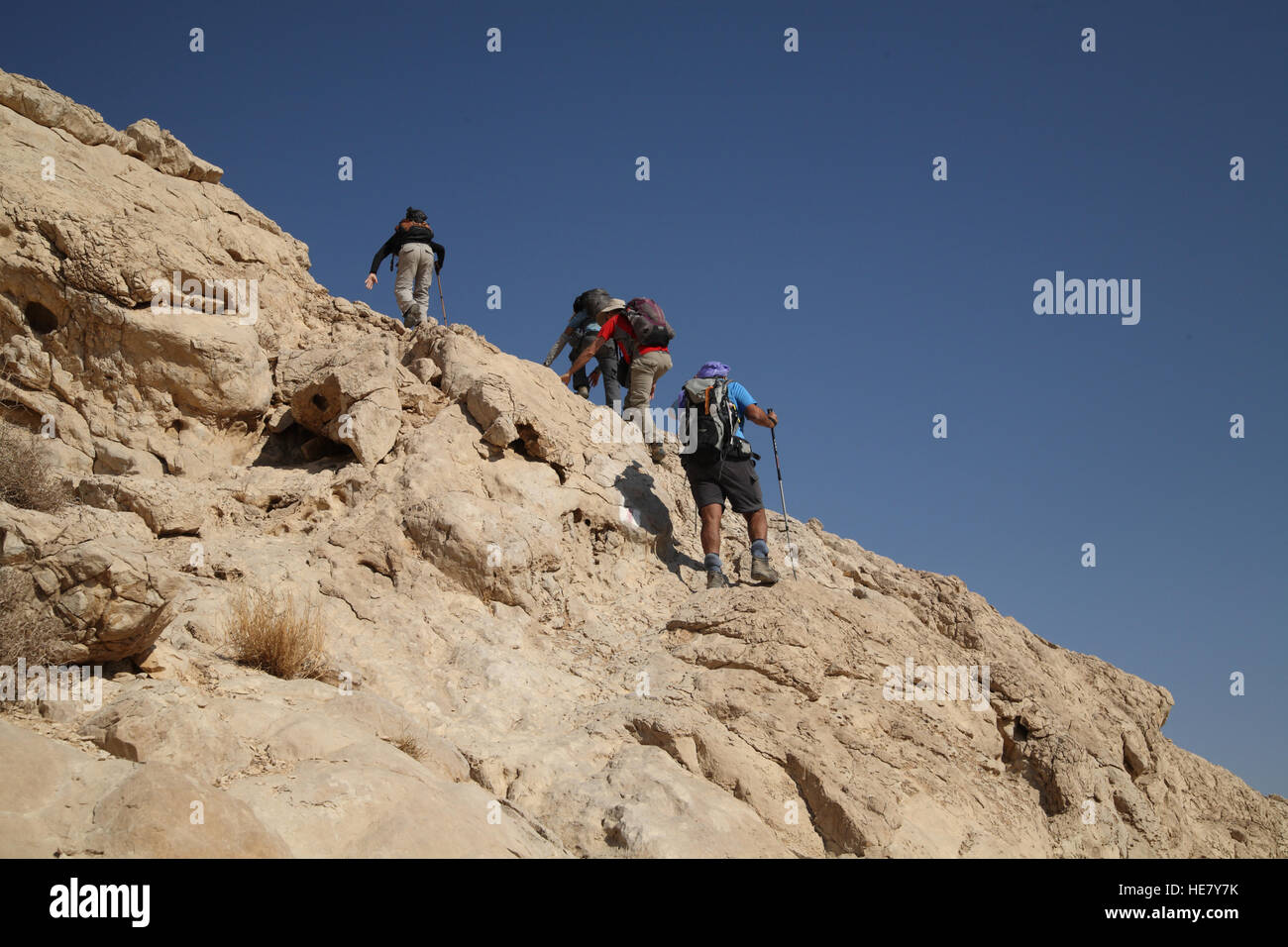 Senior citizen hikers are using sticks and hands in support while climbing a steep rocky cliff ahead of them in - Stock Image
