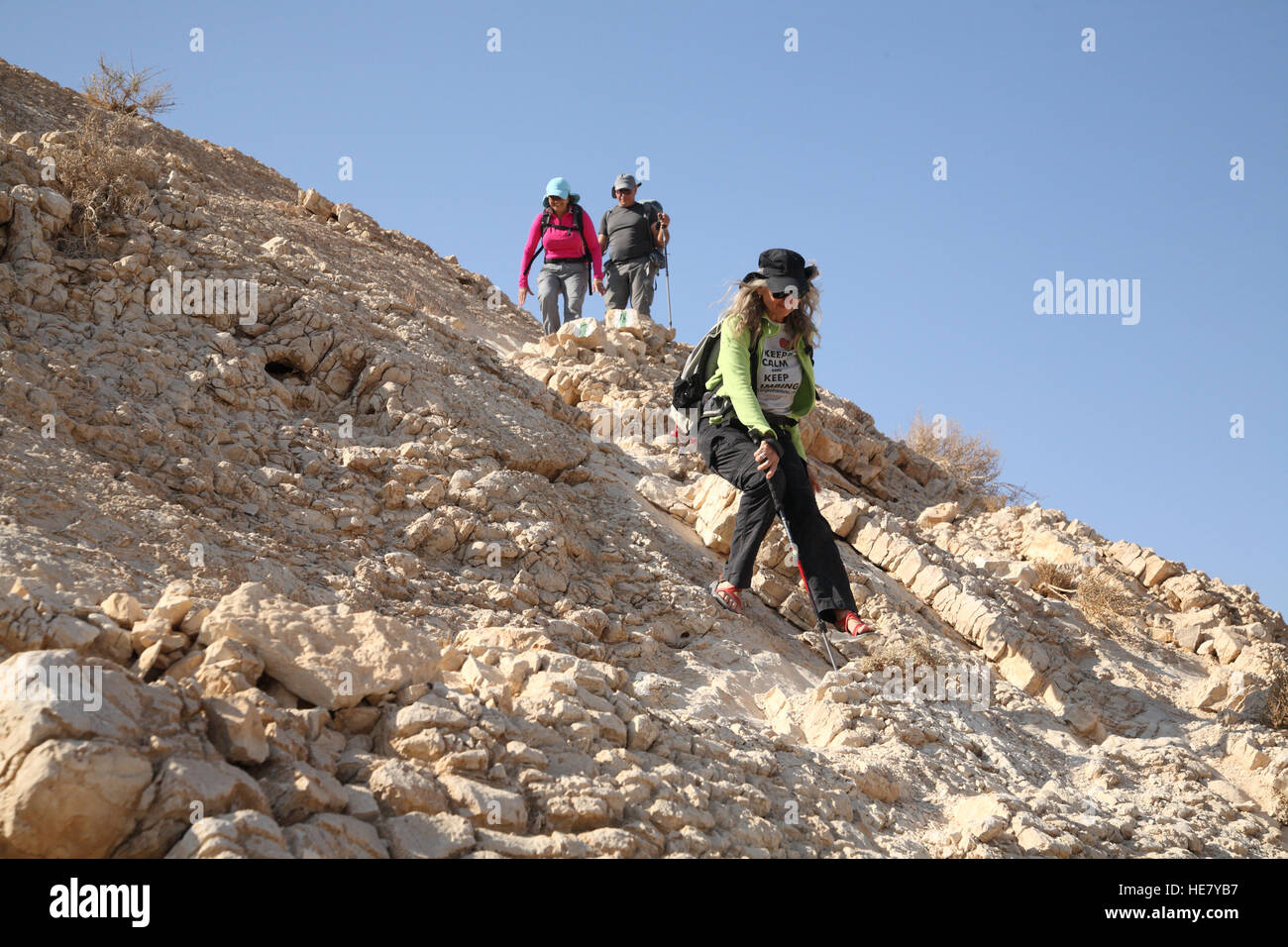 A senior citizen woman hiker descends carefully a very steep rocky slope from Mount Massor using a hiking stick - Stock Image