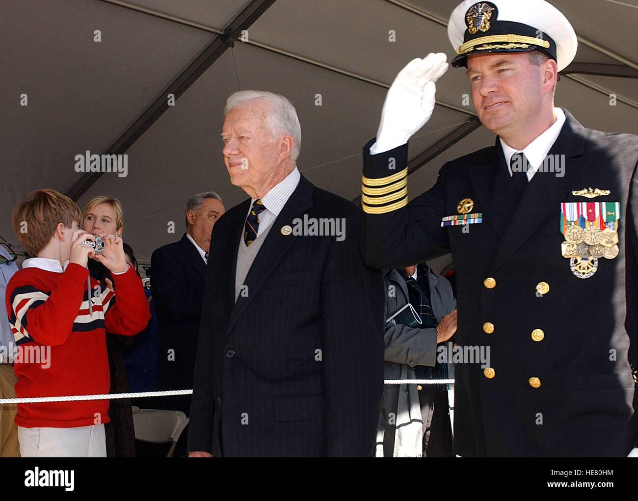 USN Commanding Officer Robert Kelso escorts former U.S. President Jimmy Carter past a crowd at the commissioning - Stock Image