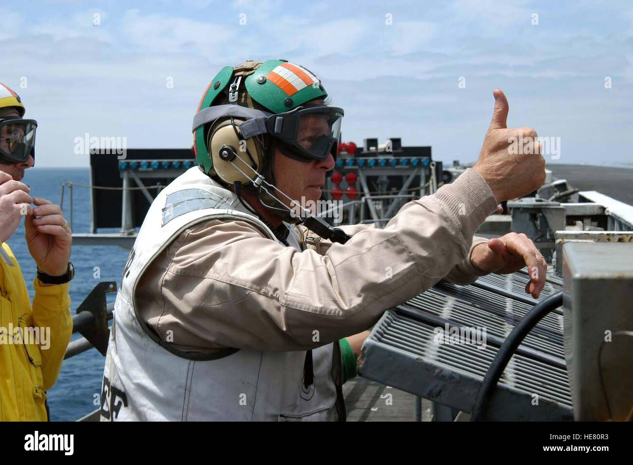 U.S. President George W. Bush gives a thumbs-up to aircraft preparing to launch from the flight deck aboard the Stock Photo