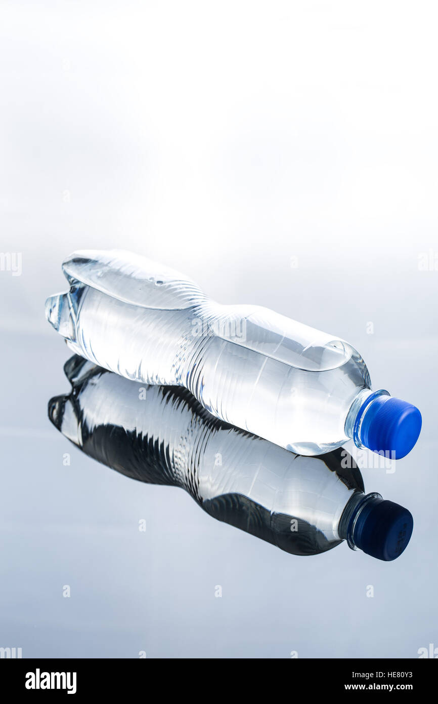 Small plastic water bottle on mirror table. - Stock Image