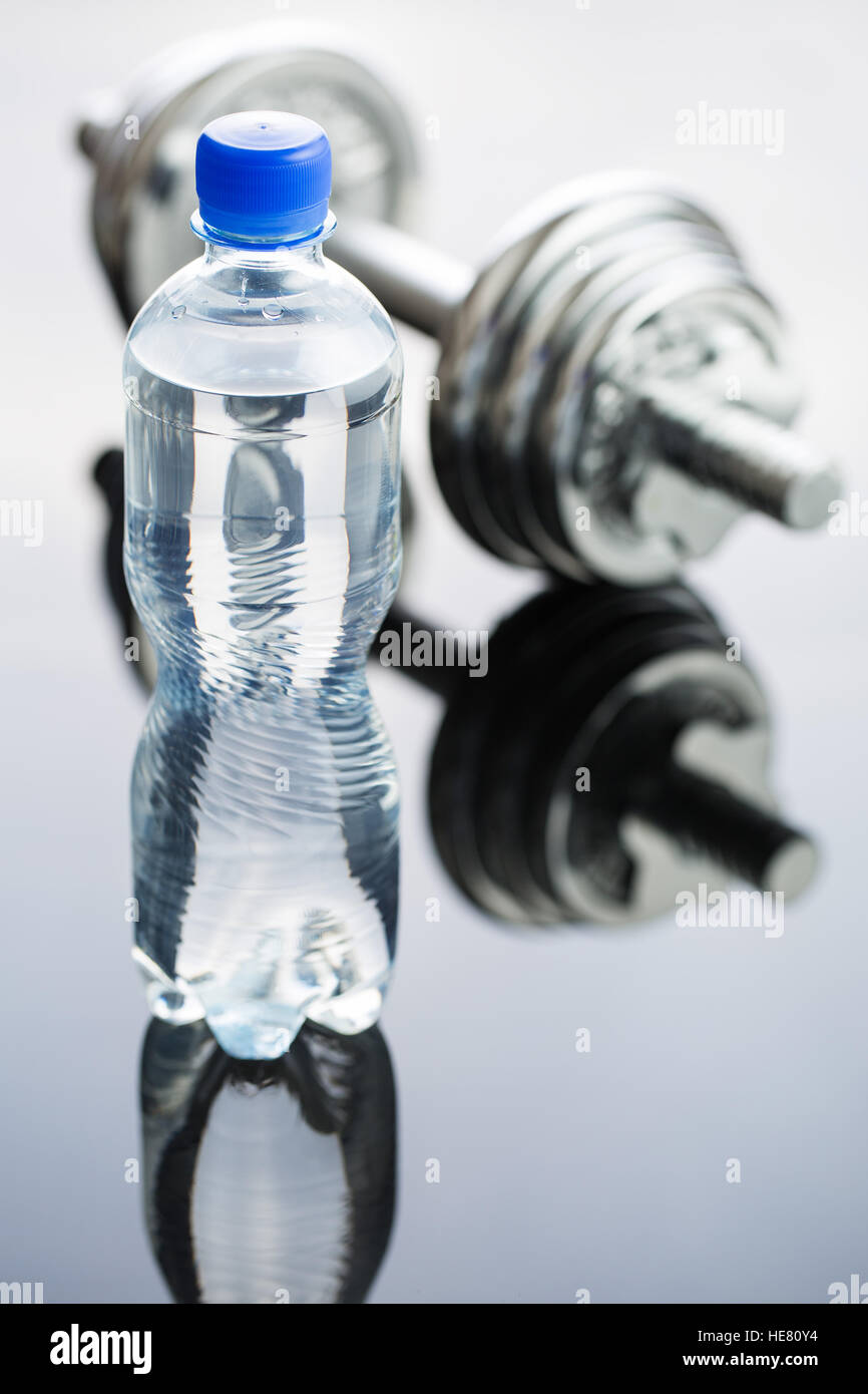 Bottle water and dumbbell on mirror table. - Stock Image
