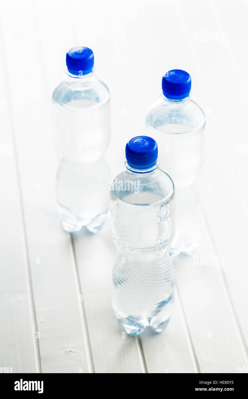 Small plastic water bottle on white table. - Stock Image