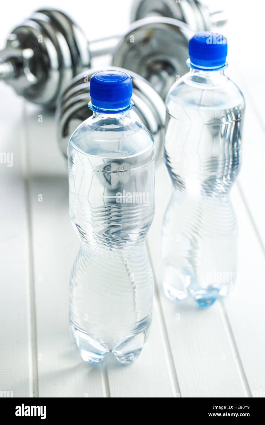Bottle water and dumbbell on white table. - Stock Image
