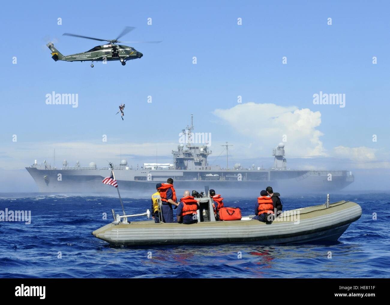 U.S. sailors on an inflatable raft watch a helicopter air lift a search and rescue swimmer from the ocean during - Stock Image