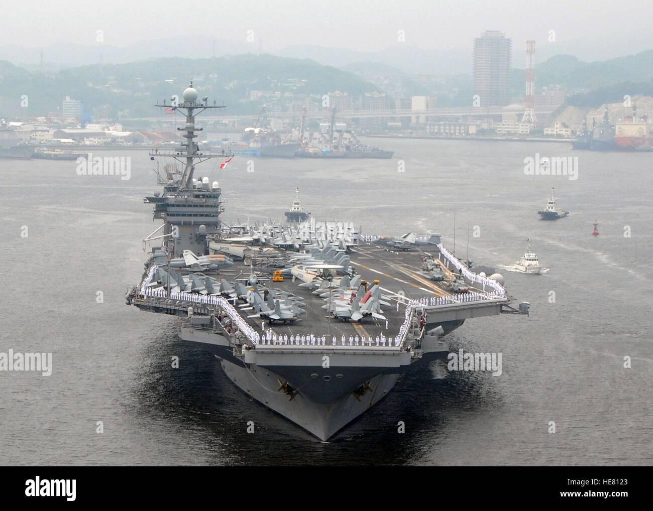 U.S. sailors man the rails aboard the USN Nimitz-class aircraft carrier USS George Washington as it departs the - Stock Image