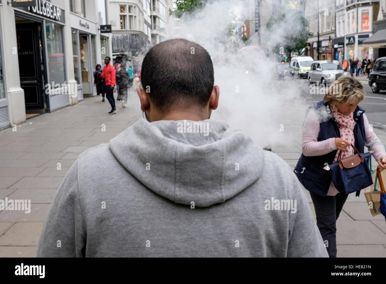 Man exhales e-cigarette smoke causing passer by to take evasive action. - Stock Image