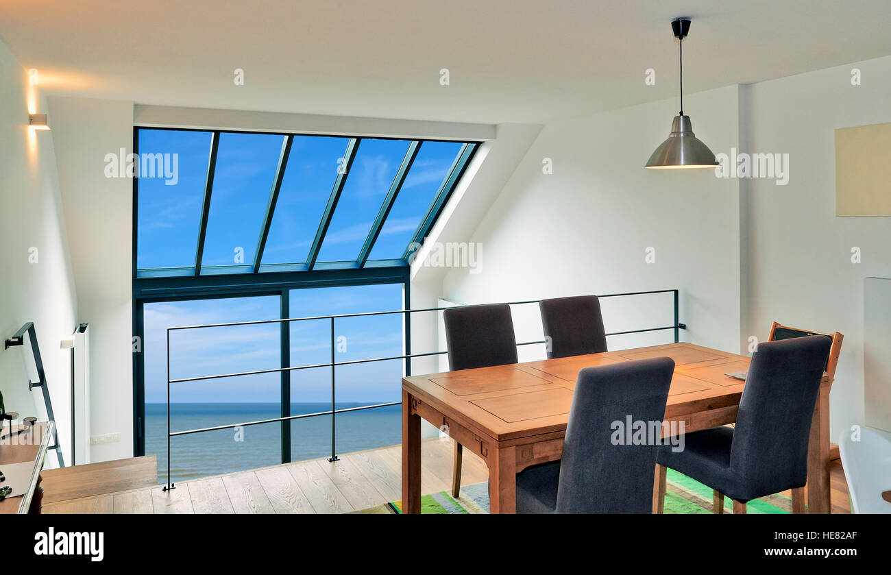 Dining table in modern duplex with large windows and sea - Stock Image