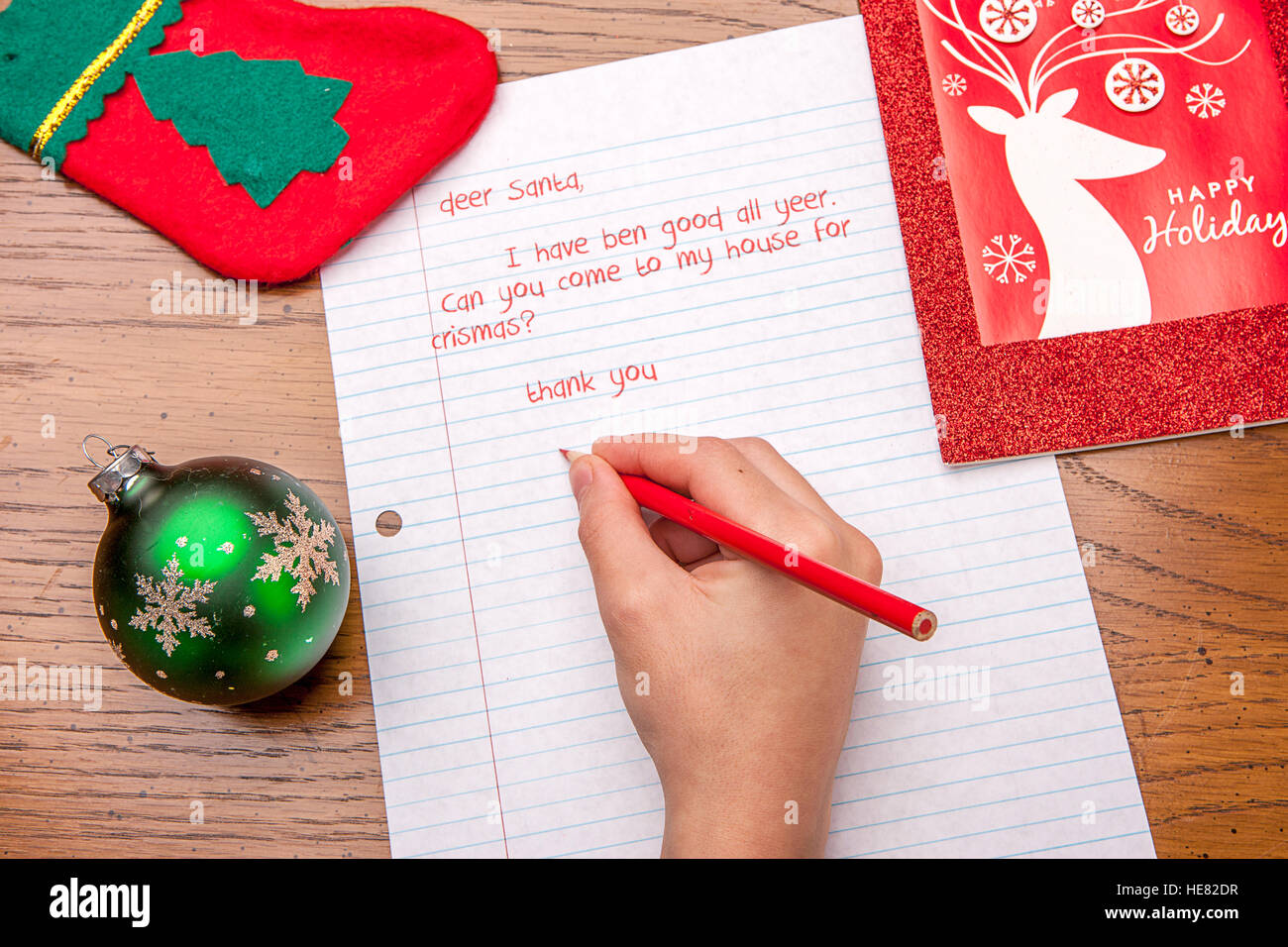 Picture of a child's hand writing a letter to Santa. - Stock Image