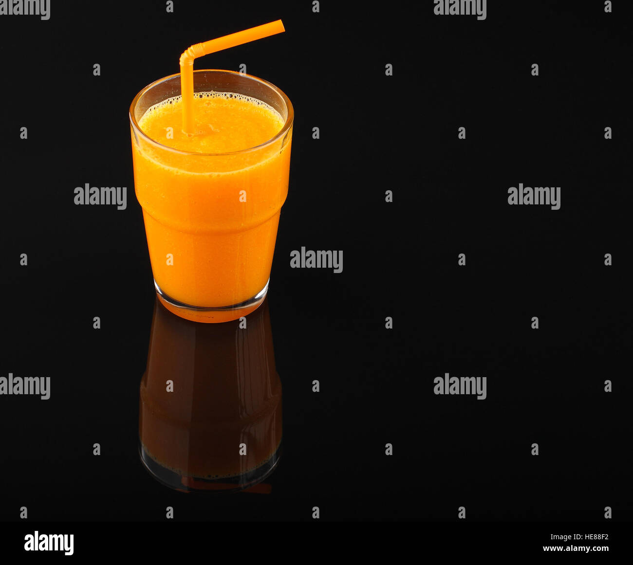 pumpkin smoothie in glass with drinking straw on black