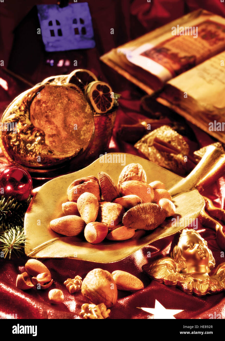 Mixed nuts on a golden plate, christmas atmosphere - Stock Image