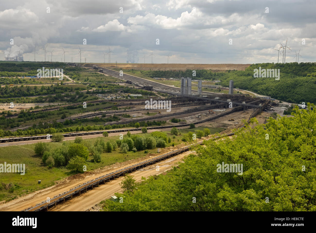 Parts of Garzweiler surface mine, shot from Jackerath viewpoint, with power plants and wind turbines behind. - Stock Image