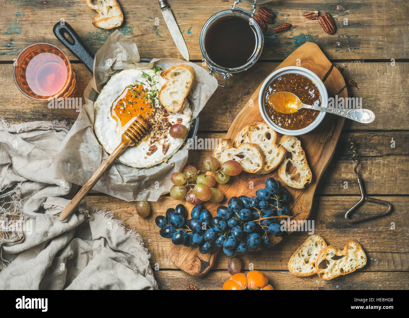 Cheese, fruit, nut and wine set over rustic wooden background - Stock Image