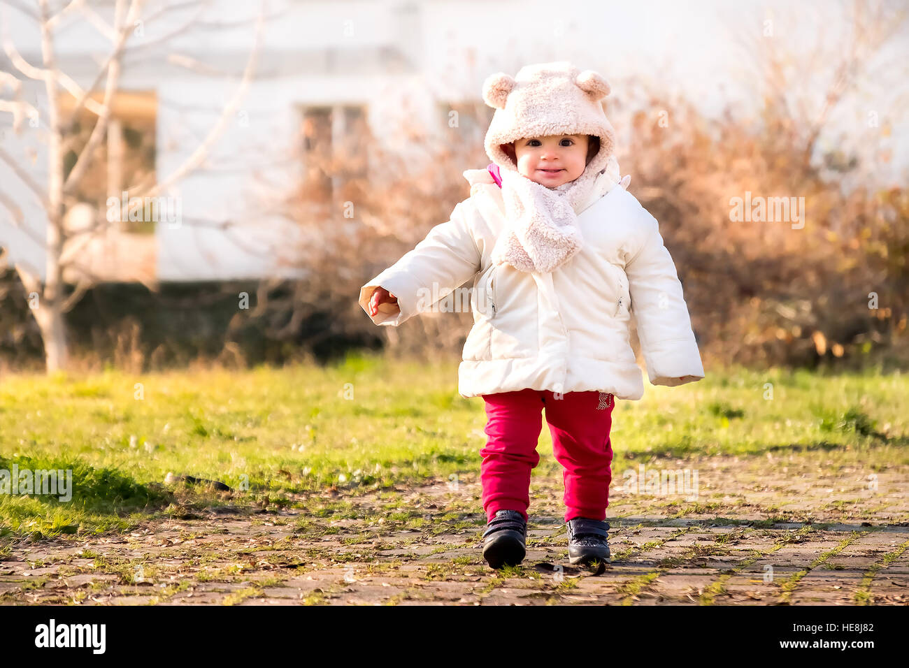 baby cap with ears newborn walking park winter dressed first steps - Stock Image