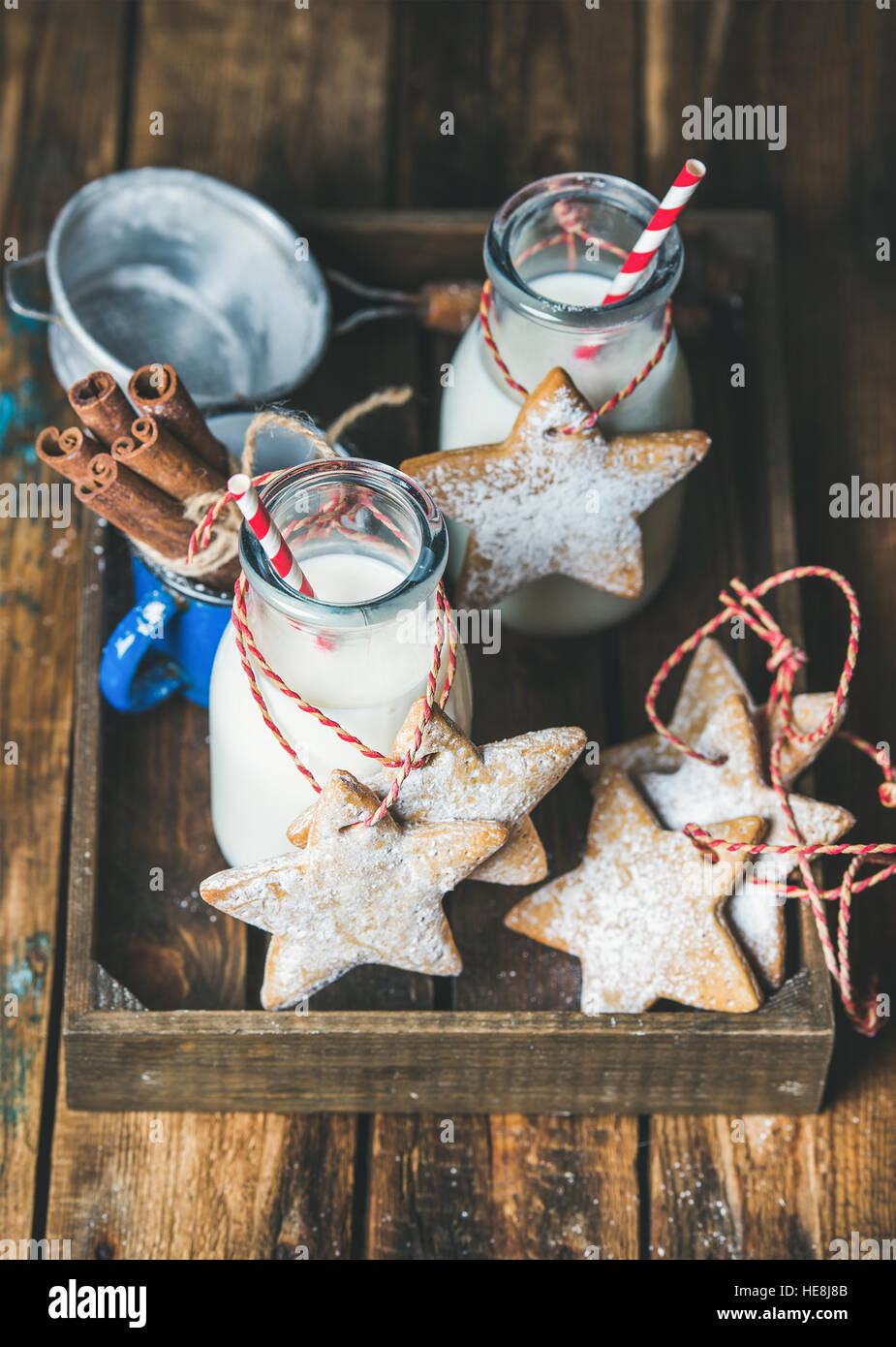 Bottles with milk for Santa and Christmas homemade gingerbread biscuits - Stock Image