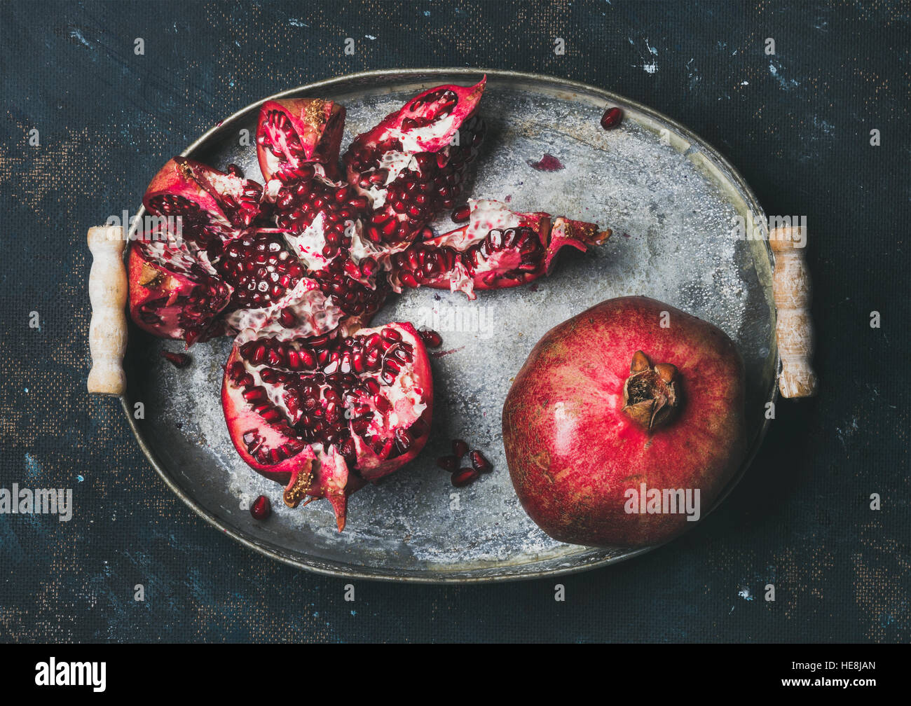 Fresh ripe pomegranate broken in metal tray over plywood background - Stock Image