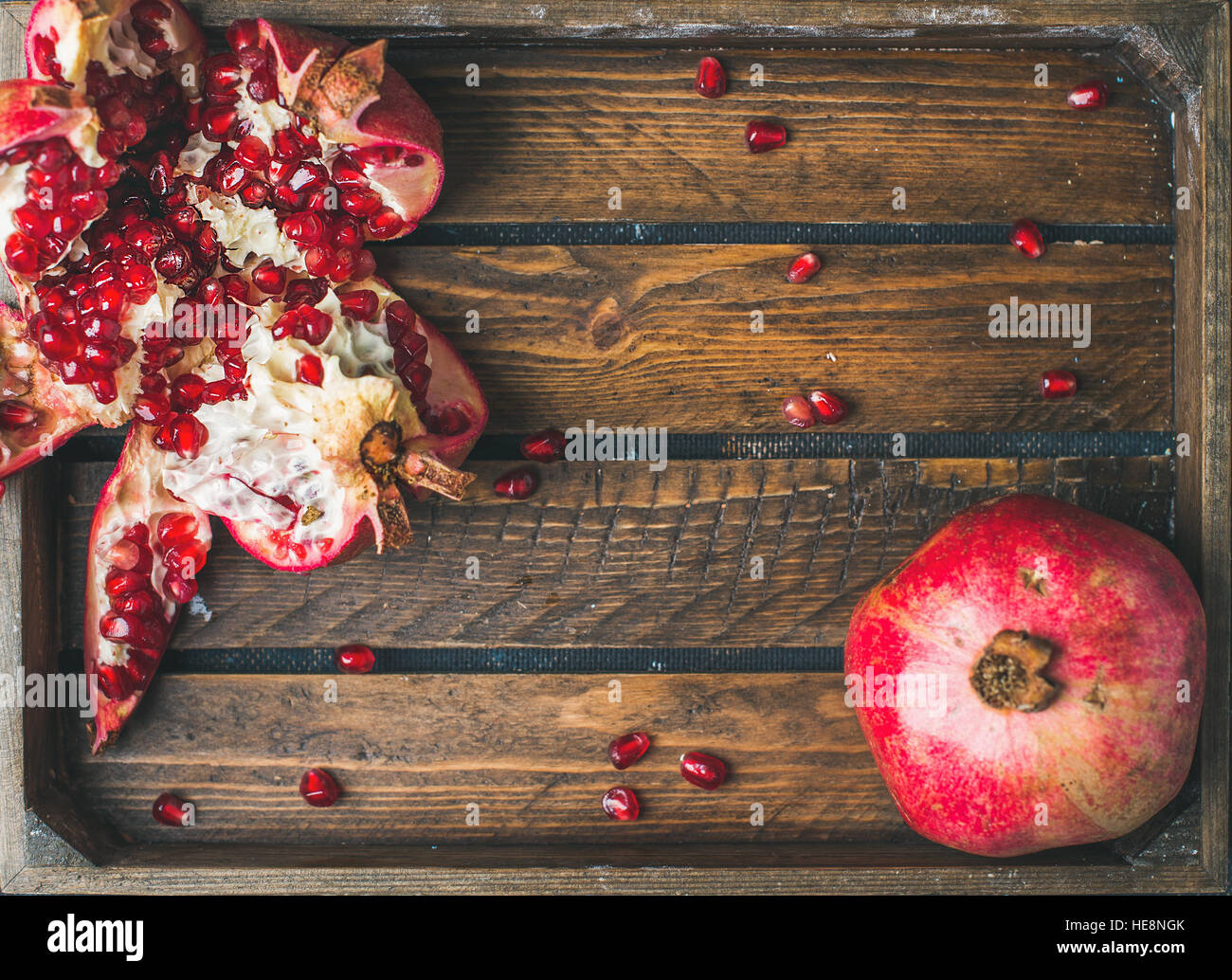 Fresh ripe pomegranates, one cut in pieces in wooden tray - Stock Image