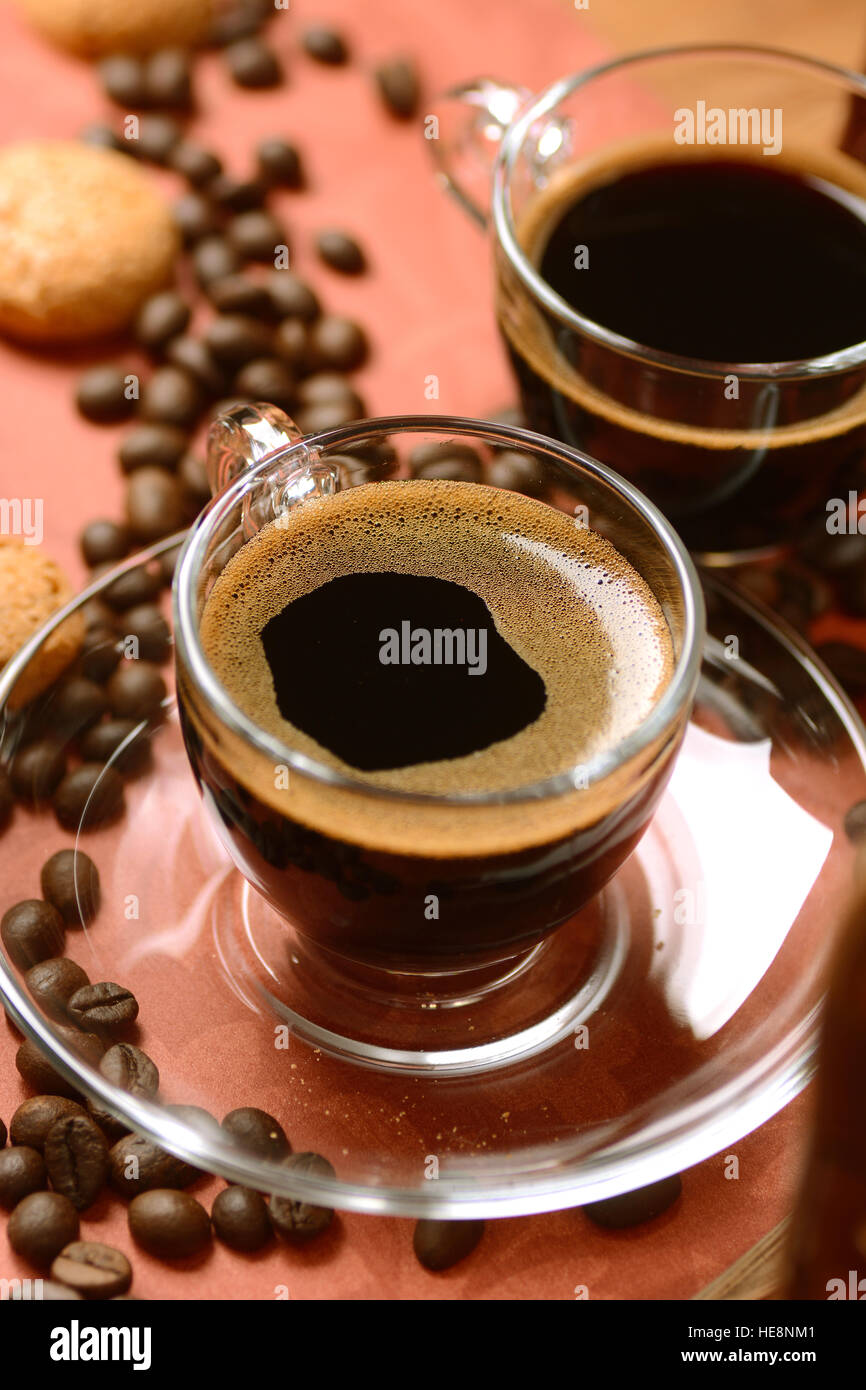 Italian espresso coffee in glass cup with amaretti biscuits around - Stock Image