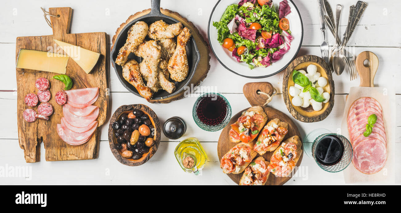 Rustic table set with chicken, salad, different snacks and wine - Stock Image