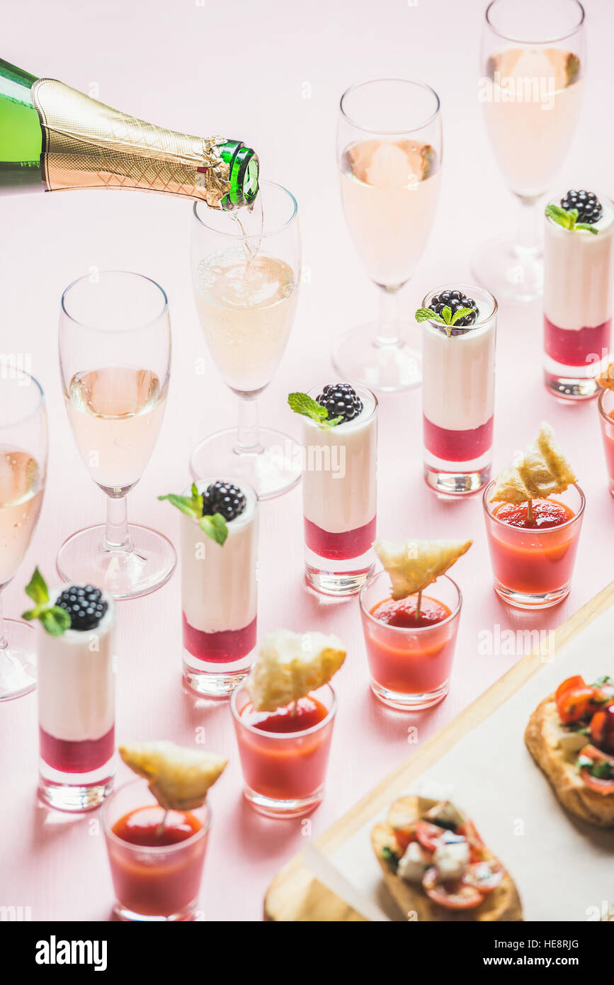 Various snacks, brushettas, gazpacho shots, desserts, champagne pouring to glasses - Stock Image
