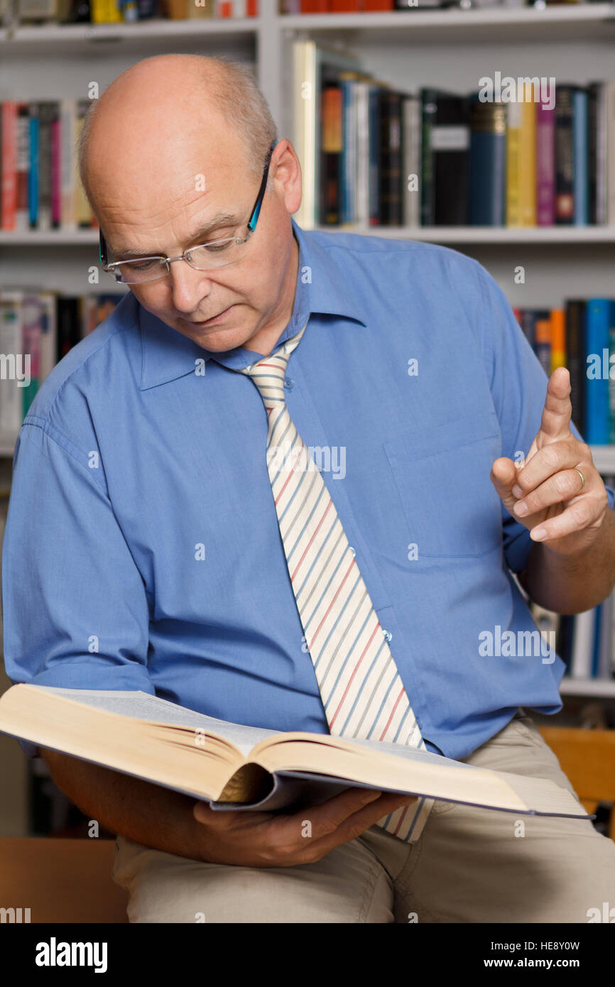 Senior teacher or professor in front of a bookshelf in a library reading aloud out of a book while holding up his - Stock Image