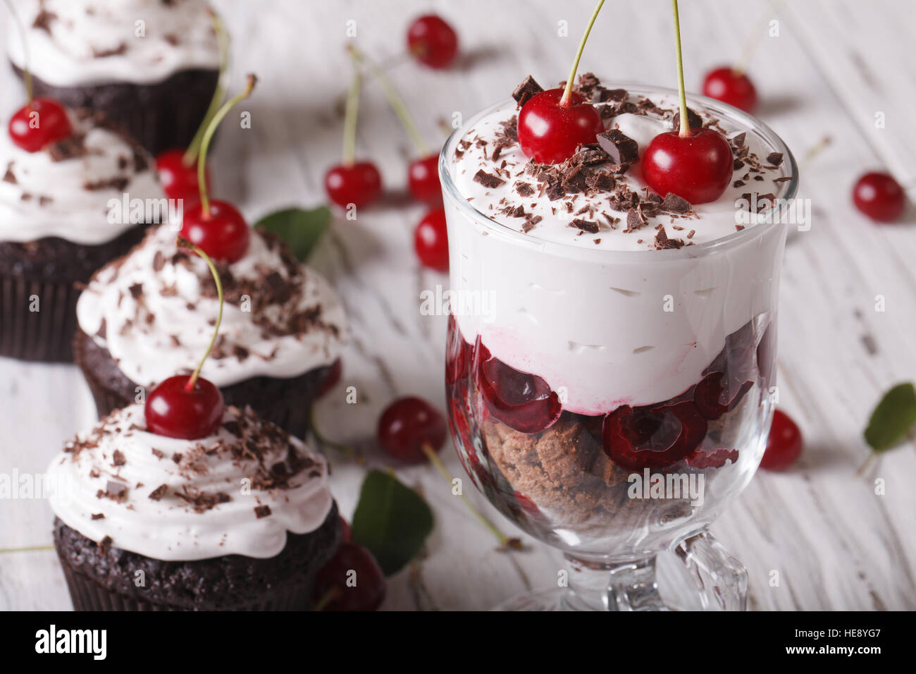 Dessert cherry black forest and cupcakes on a table close-up. horizontal - Stock Image