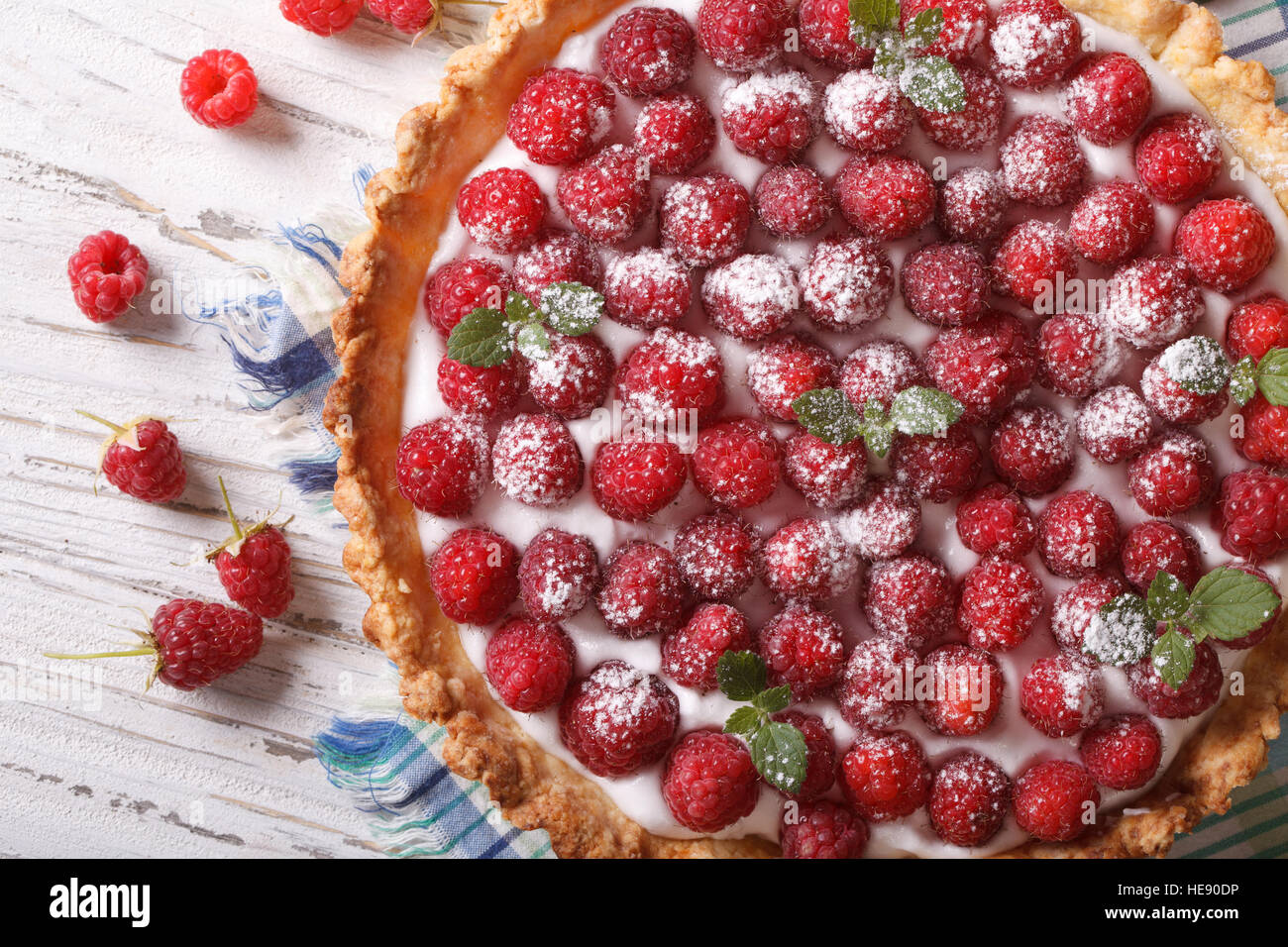 Homemade raspberry tart with cream close-up. horizontal view from above - Stock Image
