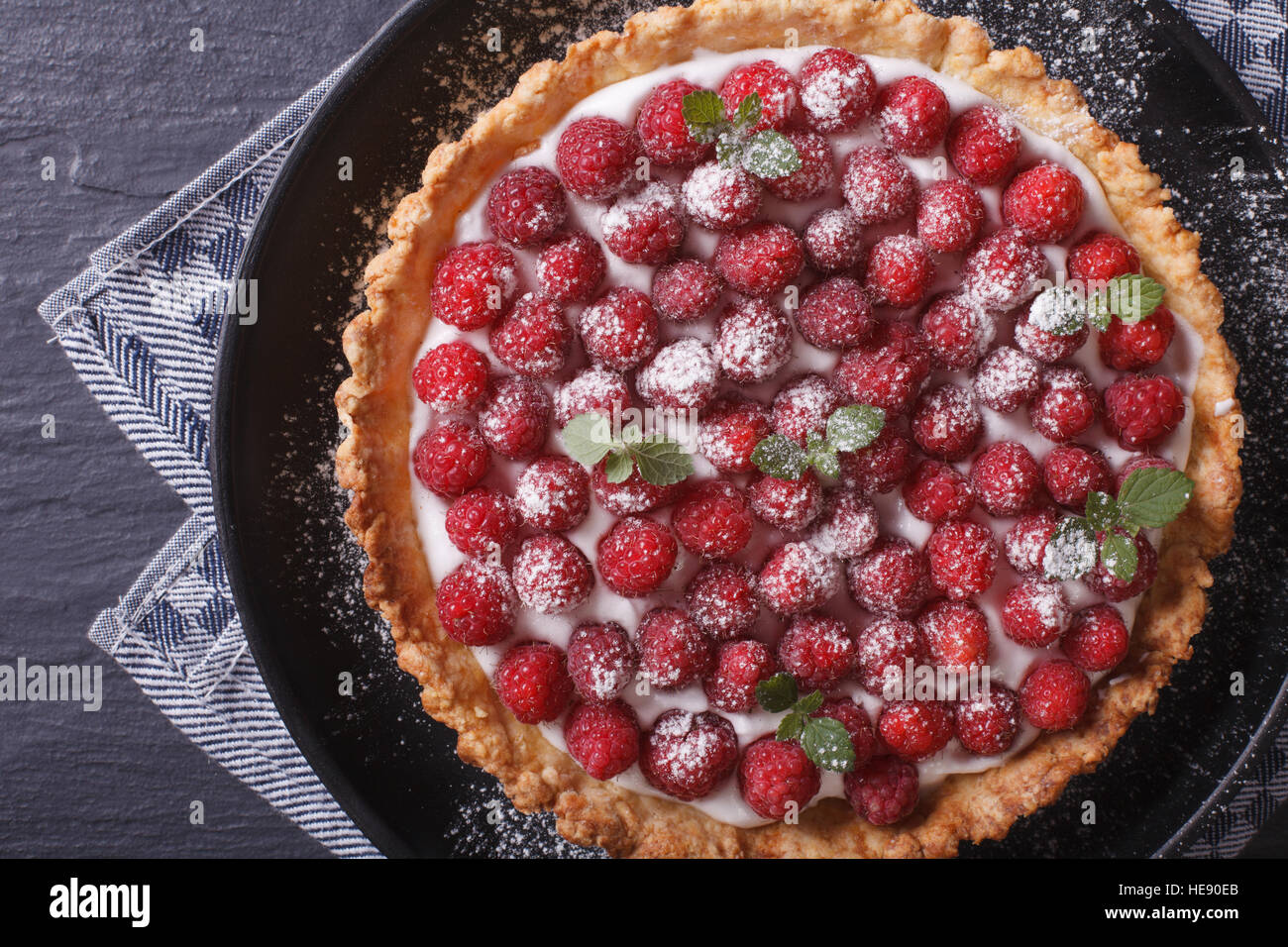 Gourmet raspberry tart with whipped cream on a plate close-up horizontal view from above - Stock Image