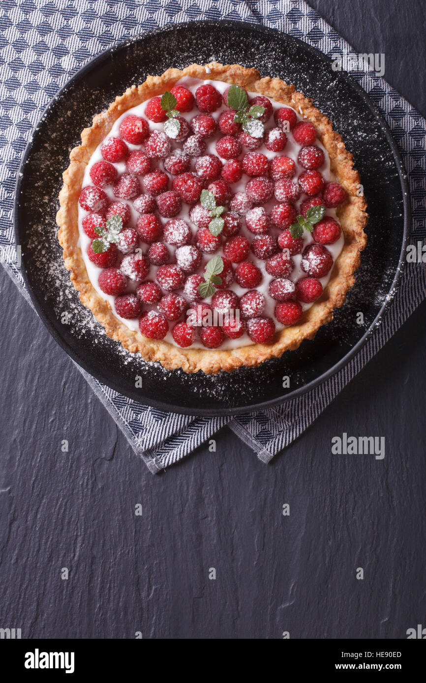 Delicious raspberry tart with whipped cream on a plate vertical view from above - Stock Image