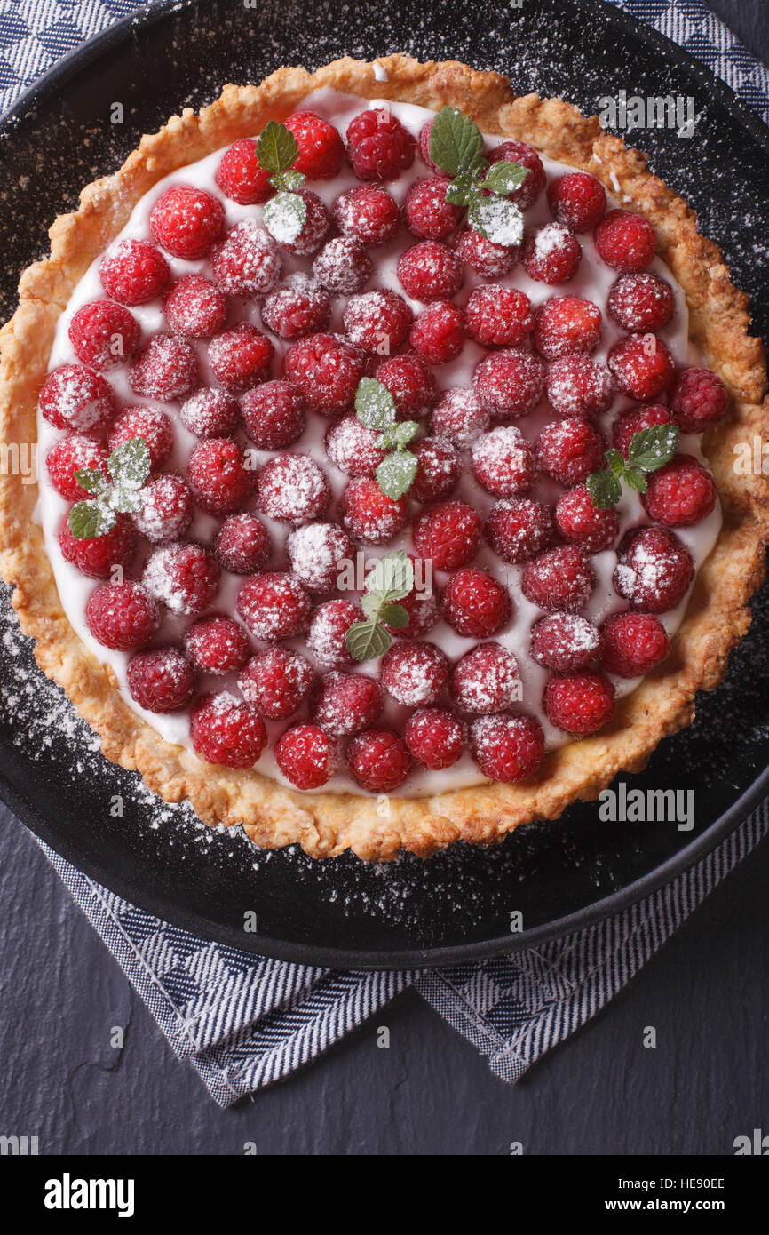 Delicious raspberry tart with whipped cream on a plate close-up vertical view from above - Stock Image