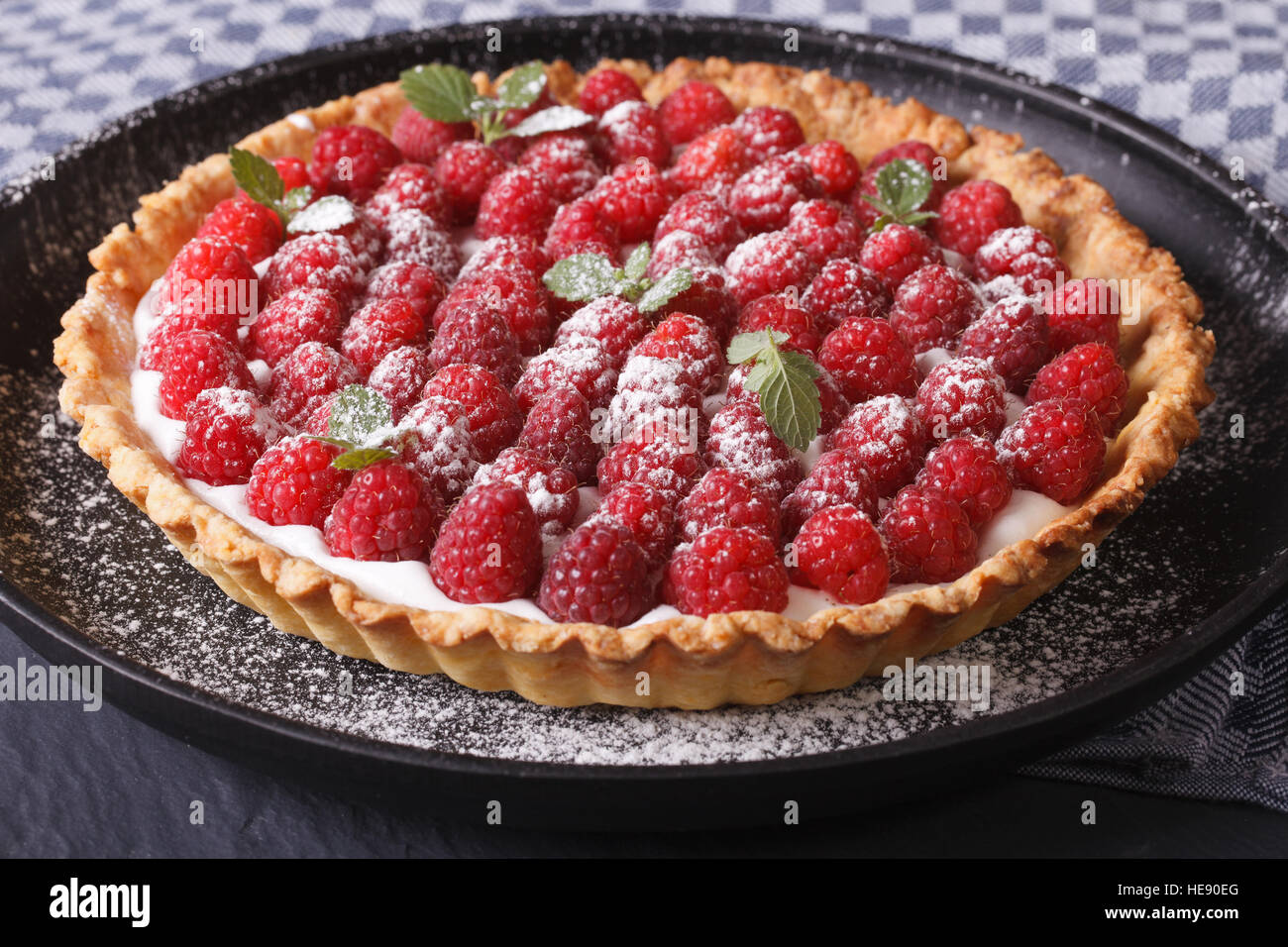 Delicious tart with fresh raspberries and mint on a plate close-up horizontal - Stock Image