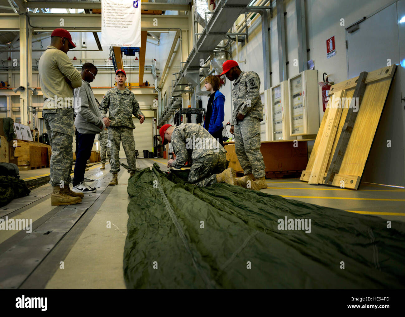 U.S. Army parachute riggers show Aviano Middle/High School students a heavy equipment parachute during job shadow - Stock Image