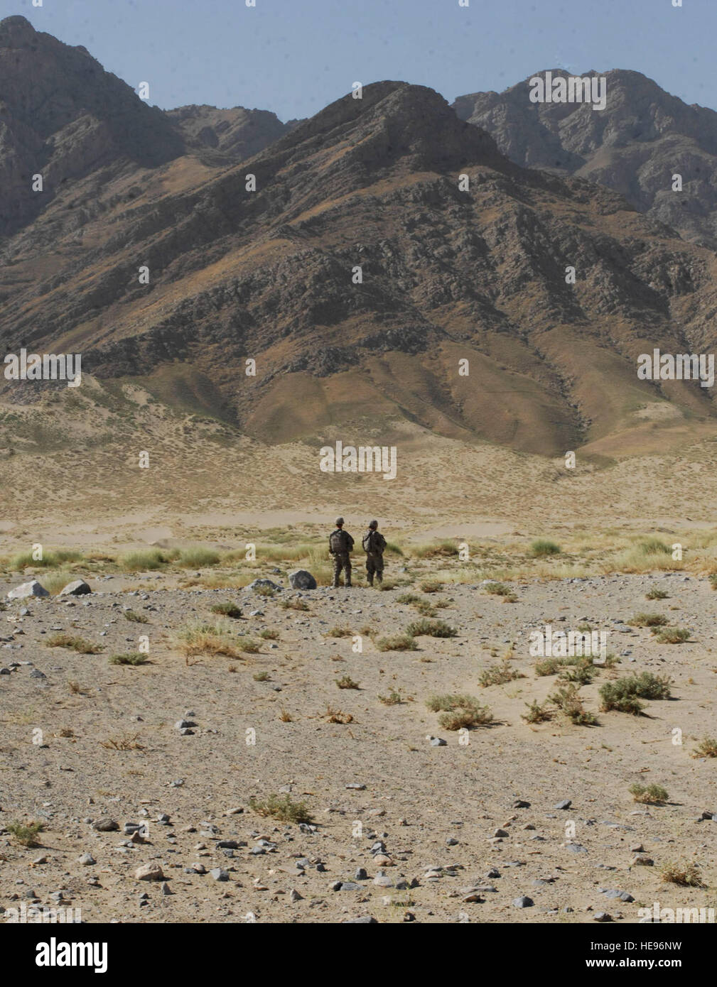 Against the bacdrop of mountains in Afghanistan, two soldiers from Combined Joint Task Force-82 provide security - Stock Image