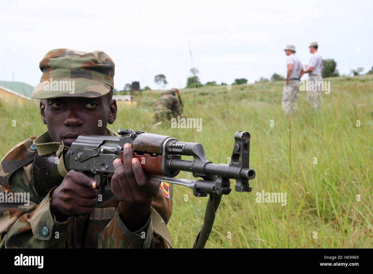 A Ugandan Peoples Defense Force Student Soldier Maintains Security While Other Members Of His Team Provide