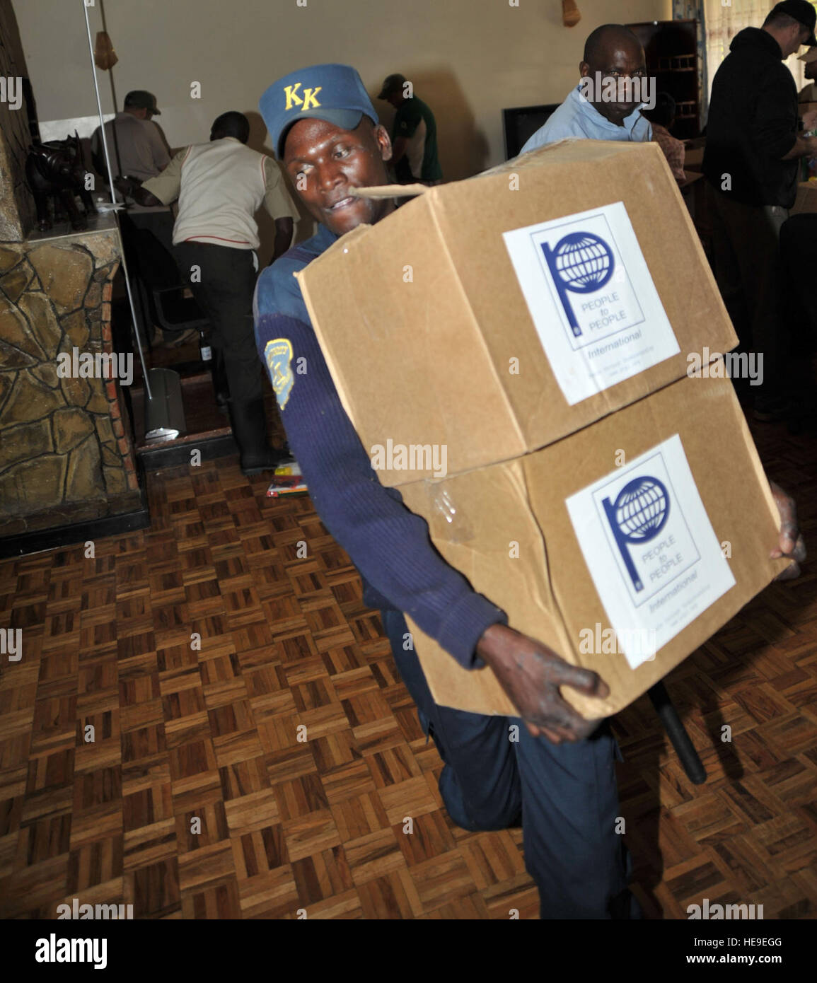 John Onyango, a guard with KK Security, helps load boxes of school supplies donated by People to People International Stock Photo