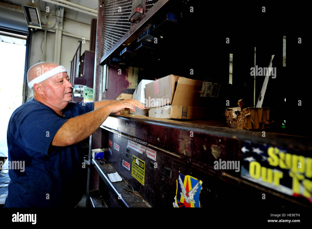Scott Hallas, 1st Special Operations Civil Engineer Squadron, rearranges recyclables in a compactor at the recycling - Stock Image