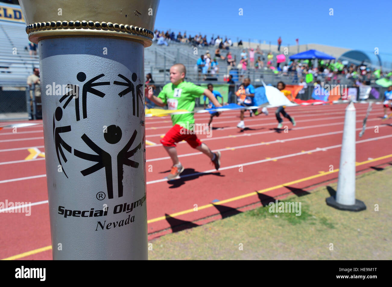 Children competing in the 50-meter race pass the Nevada Special Olympics torch at Cheyenne High School in Las Vegas - Stock Image